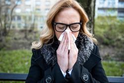 Woman sneezing and holding paper tissue. Flu season. Allergy season. Corona virus