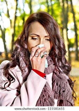 Woman sneezing handkerchief fall outdoor. - stock photo