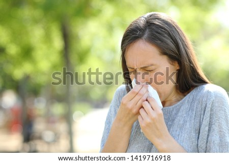 Woman sneezing using a wipe standing outdoors in a park #1419716918
