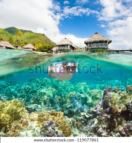Woman snorkeling in clear tropical waters in front of overwater bungalows
