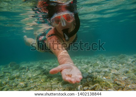 Woman snorkeling in shallow sea. Female swimmer with diving mask and snorkel showing shell into camera. #1402138844