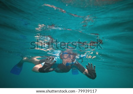 Woman snorkeling in the open ocean looking curiously at something