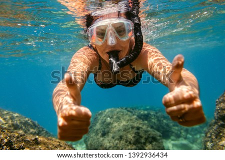 Woman snorkelling under water. Female swimmer with diving mask and snorkel giving thumbs up in sea. #1392936434