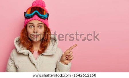 Woman snowboarder dressed in warm clothes, points fore finger on blank space, wears ski glasses, shows something for winter rest, poses against pink background. Extreme sport, leisure, spare time