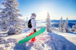 Woman snowboarder holds snowboard against background of winter forest and snow, ski resort sunlight. Adventure concept active leisure.