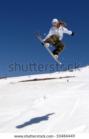 woman snowboarder in air flowing jump holding board with sky and shadow.