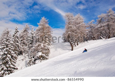 Woman snowboarder relaxing/Young snowboarder sitting  on snow with beautiful winter landscape in the background