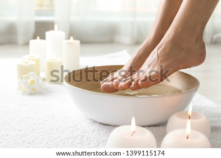 Woman soaking her feet in dish indoors, closeup with space for text. Spa treatment Stock photo ©