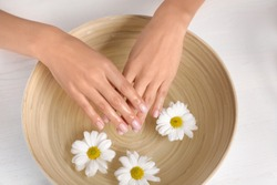 Woman soaking her hands in bowl with water and flowers on wooden table, top view. Spa treatment