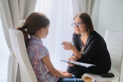 Woman social worker talking to girl. Child psychology, mental health.