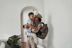 Woman soldier laughing and holding her son at the hands after returning home