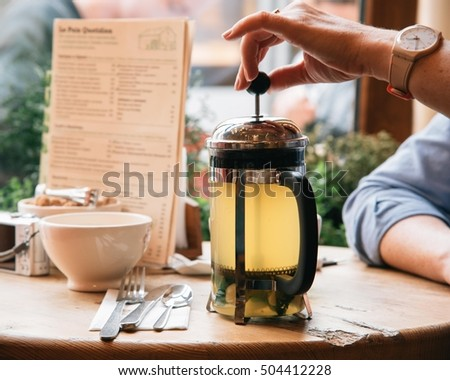 woman spent her coffee break at the organic cafe and prepare tea in french press