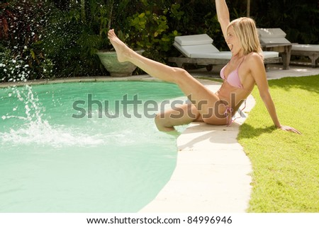 Woman splashing water with her feet while sitting by hotel's swimming pool.
