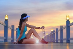 woman sport runner sitting on the wooden sea bridge holding drinking water in hand, resting or paused jogging for a while on the jetty, enjoy exercise jogging in sunset light