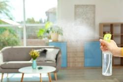 Woman spraying air freshener at home