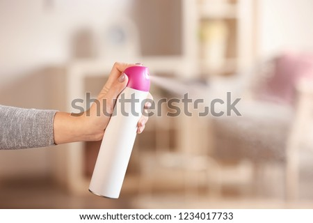 Woman spraying air freshener at home #1234017733