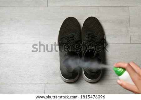Woman spraying deodorant over pair of shoes at home, closeup. Space for text Foto stock ©