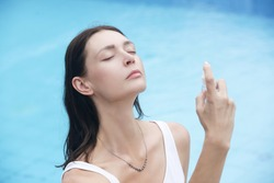 Woman spraying facial mist on her face, summertime skin care concept