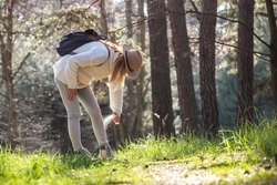 Woman spraying insect repellent against tick at her legs. Protection against mosquito bite during hike in forest