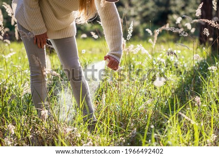Woman spraying insect repellent against tick at her legs. Protection against mosquito bite during walk in grass Photo stock ©