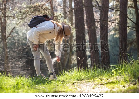 Woman spraying insect repellent against tick at her legs. Protection against mosquito bite during hike in forest Photo stock ©