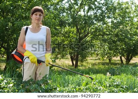 Woman spraying potato plant in field