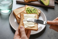 Woman spreading butter on toasted bread at table, closeup