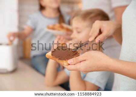 Woman spreading chocolate paste on toast, closeup #1158884923