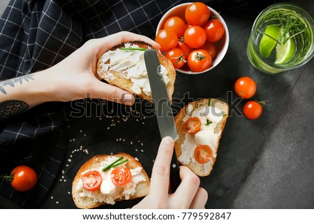 Woman spreading cream cheese on toast over table, top view