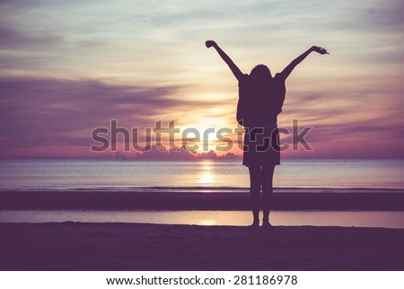 Woman spreading hands with joy and inspiration at sunrise.