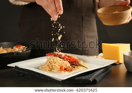 Woman sprinkling with cheese on chicken spaghetti