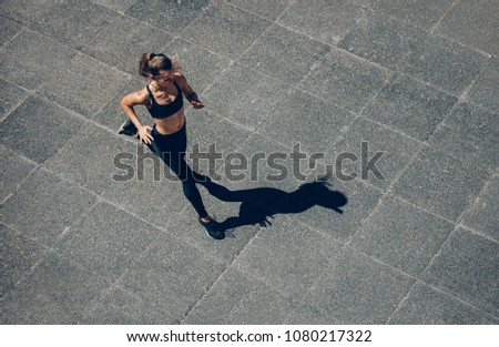 Woman sprinting in the morning outdoors. Top view of female runner working out in the city. #1080217322