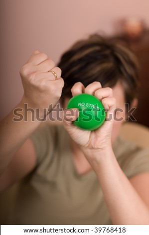 woman squeezes a green ball