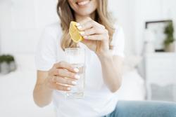 Woman squeezes lemon juice into a glass.