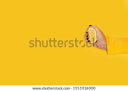 Woman squeezing a half lemon on a yellow background with copy space Stockfoto ©