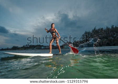 Woman stand up paddle boarding at dusk on a flat warm quiet sea