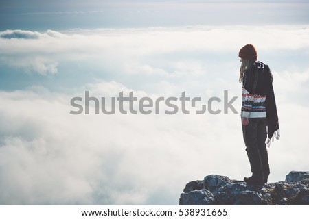 Woman standing alone on cliff over clouds landscape Travel Lifestyle concept adventure vacations outdoor happy emotions