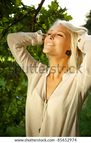 Woman standing amongst trees and enjoying the moment.