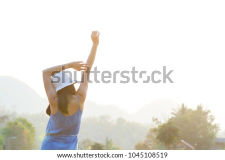 woman standing and rising hands in morning with sun light #1045108519