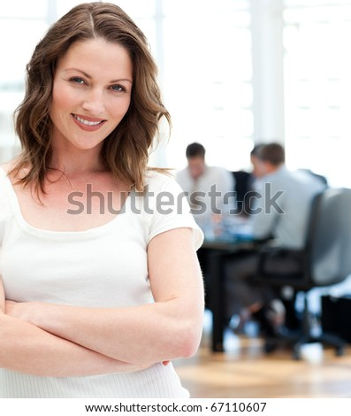 Woman standing at a meeting while her team working in the background