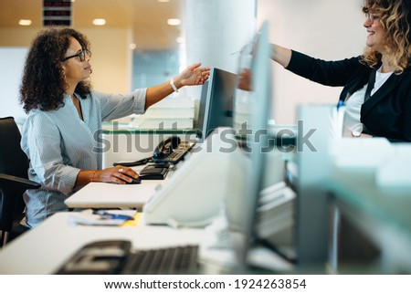 Woman standing at reception desk giving her card to the receptionist. Woman visiting municipality office being assisted by the administrator at front desk.