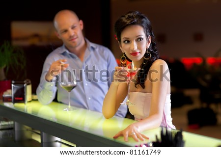 woman standing at the bar with men behind, looking at her
