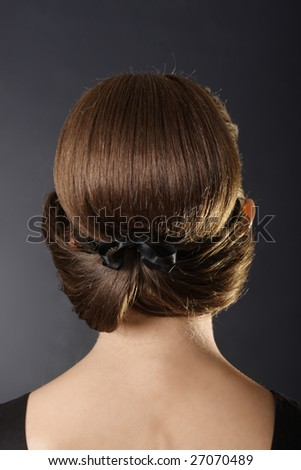 Woman standing back with classic bun hairstyle over dark