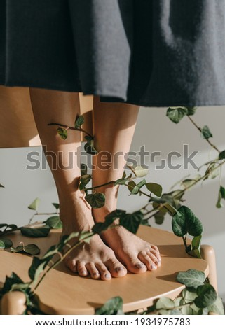 Woman standing barefoot on a wooden chair with legs tied with green leafy twigs. Interaction with nature concept. Photo stock ©