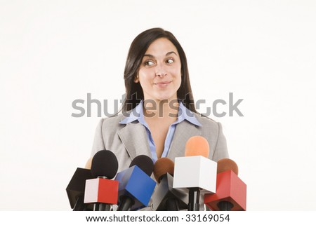 woman standing behind bank of microphones