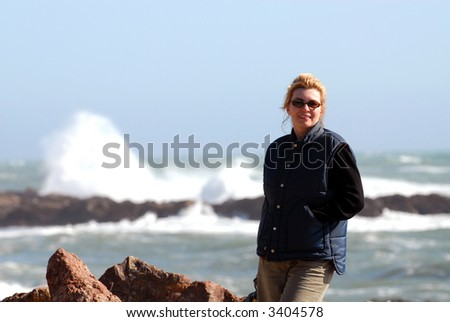 Woman Standing by Sea With Waves Crashing Behind Her