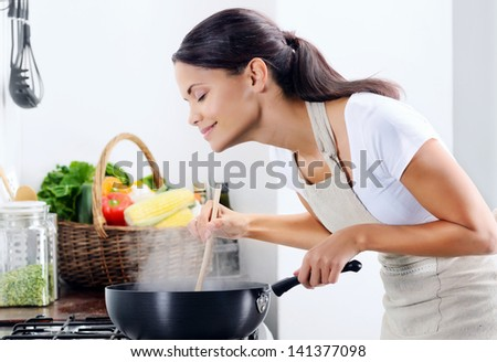 Woman Standing By The Stove In The Kitchen, Cooking And Smelling The Nice Aromas From Her Meal In A Pot