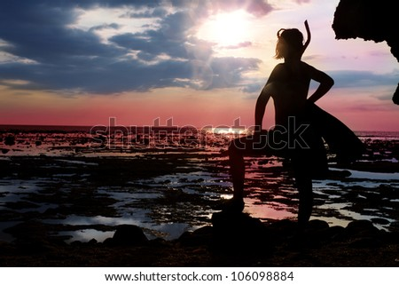 woman standing during the low tide with diving equipment  on the shore and waiting for big water in sunset