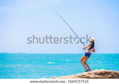 woman standing fishing on the rock at the sea #1069537526