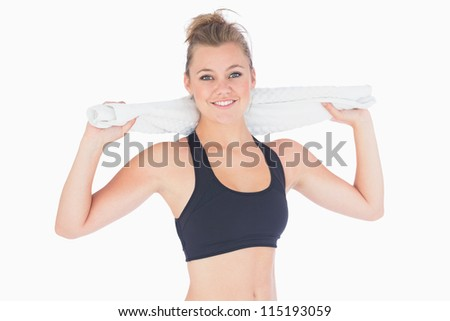 Woman standing holding a towel while smiling after workou